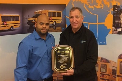 Trans Tech Sales Manager Erickson Lopez, shown left, presents the manufacturer's 2015 Distinguished Dealer Award to Western Canada Bus General Manager Doug DeHoop.