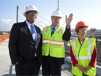 In this 2014 photo, Secretary of Transportation Anthony Foxx stands with TriMet General Manager Neil McFarlane (center) and Congresswoman Suzanne Bonamici on the Tilikum Crossing, during construction. Photo: TriMet