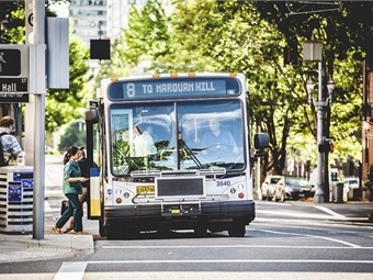 A TriMet Line 8 Jackson Park NE 15th bus with riders boarding. Photo: TriMet