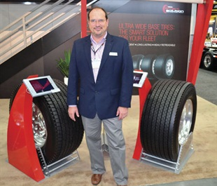 Rick Phillips, senior director of commercial and OTR sales for Yokohama Tire Corp., says the 902L Ultra Wide Base regional drive tire (left) has a 27/32nd-inch tread depth. It will be available by mid-year. The 709L Ultra Wide Base drive tire (right) is more fuel efficient; it has a shallower tread depth and will be available in the fourth quarter.