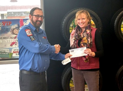 Paul Boundreau, district manager for VIP Tires & Service, presents a $3,035 check to Lebanon Schools Superintendent Joanne Roberts.