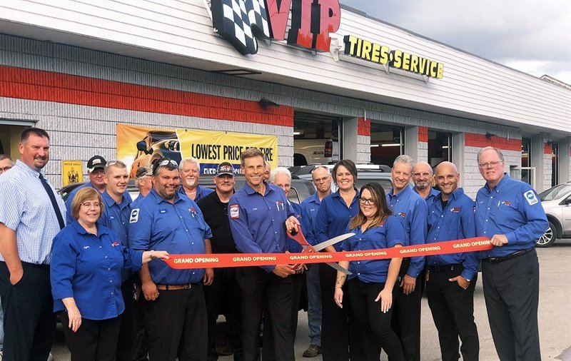 VIP Tires & Service President and CEO Tim Winkeler (center) cuts the ribbon at the re-opening of the company's newly renovated store in Brunswick, Maine. He's joined by Chairman of the Board, John Quirk (right), and the entire Brunswick auto store team.