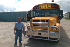 Every school day, bus driver Dale Westover travels to and from Canada on a remote route and checks in with U.S. and Canada customs several times. Shown here is Westover with his bus, outfitted with a grill guard designed to prevent damage from collisions with deer.