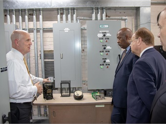 SEPTA GM Jeffrey Knueppel (left) shows U.S. Rep. Dwight E. Evans (second from right) and APTAPresident/CEO Paul P. Skoutelas (right) the circa 1930s electrical equipment used by SEPTA at its Wayne Junction substation to power its Regional (commuter) Rail lines. Funding from a Federal TIGER grant allowed SEPTA to renovate the substation with state-of-the-art equipment. (Photo by Adam N. Dall)