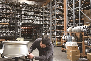 """Manager Vahé Michaelian inspects a wheel in 1-880EveryRim — OEM Wheels' Santa Fe Springs, Calif., warehouse. """"We check the wheels both when we buy and when we sell,"""" says owner Billy Eordekian."""