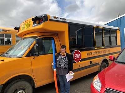Willow Creek (Mont.) School District J1517 has reopened, with safety precautions, and is offering bus service. Shown here is bus driver Chrystal Duvall, holding a pool noodle, which school staff use to demonstrate 6 feet for social distancing. Photo courtesy Willow Creek School District J1517
