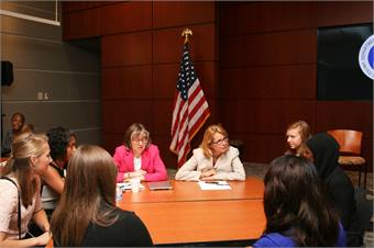 Barbara McCann, Director of the Office of Safety, Energy and Environment in the Office of the Secretary of Transportation, and Administrator Anne Ferro of the Federal Motor Carrier Safety Administrator, speak with a small group of girls and their mentors about their roles in the industry.