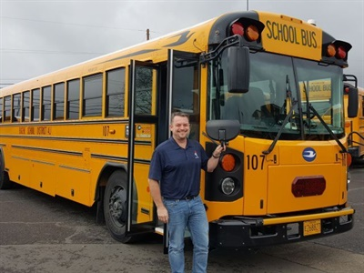 """Transportation Manager Chris Ellison shows off an upgraded """"yellow charter"""" school bus."""