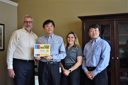 The Yokohama truck tire factory was named 'best overall industry' by the Daily Times Leader. The newspaper's publisher, Joe Robertson, left, presented the award to, from left, Osamu Zushi, president; Stacey Perusse, senior human resources manager; and Takashi Maki, senior advisor of administration. (Photo credit: Daily Times Leader)