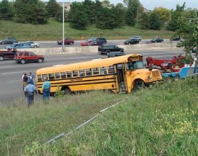 After the engine shut down on a steep grade, a school bus rolled backward about 300 feet before it jolted  to a stop in the exit lane of a freeway.