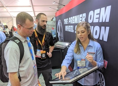 Samantha Maloy, right, from Blackburn OEM Wheel Solutions, talks with Robert Tarr, left, and Heath Hobgood from Texas Body & Frame in Lubbock, Texas.