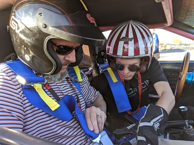Brian Decker, left, category manager at U.S. AutoForce, gets buckled in with the help of Patrick Carson, a Lone Star Drift series driver sponsored by Kenda, at the SpeedVegas track.