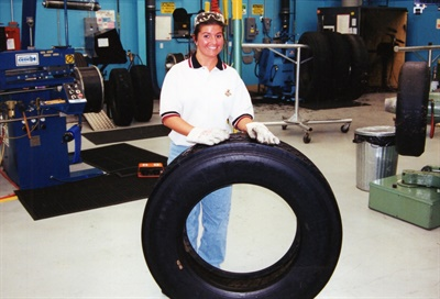This young female trainee was so proud of her retread that she wanted her own picture with it.