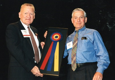 Marvin Bozarth, former ITRA executive director (on left), hands a Best in Show Award to the late Harvey Brodsky, former managing director of the Tire Retread & Repair Information Bureau (TRIB), on behalf of one of his members who could not accept the award in person.