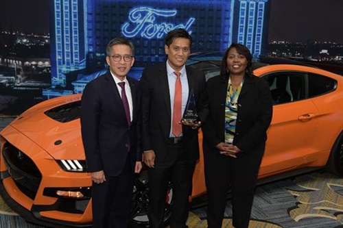 Pirelli's Ernest Bedia, center, accepted a Brand Pillar of Sustainability World Excellence Award from Ford's Hau Thai-Tang, left, and Linda Cash, vice president of quality and new model programs.
