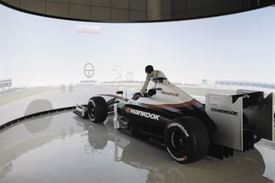 The driving simulation room features a race car parked in front of a large curved screen that offers a 360-degree view. The simulator primarily tests handling, but braking and other variables also are measured.