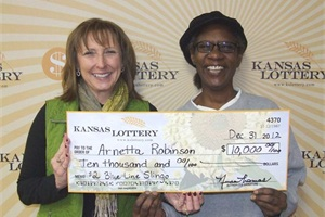 Neysa Thomas (left), deputy director of the Kansas Lottery, presents bus driver Arnetta Robinson with a ceremonial $10,000 check in recognition of her win.