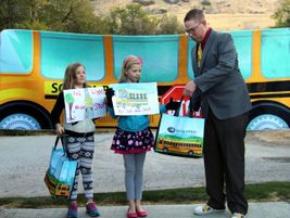 Michael Benedict, the event coordinator for the Utah State Board of Education, presents gift...