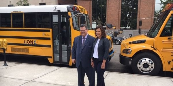 Seven Michigan districts will receive funds to buy electric school buses. Shown here is Gov....