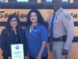 Salena Torres, school bus driver for Southwest Transportation Agency (center), received the North Region School Bus Driver of the Year award from the California Highway Patrol (CHP) and the California Department of Education. Photo courtesy Victor Taylor, public information officer for the CHP