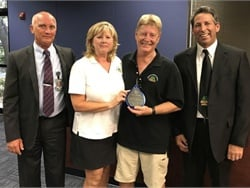 Driver Dan Dunn and attendant Chris Dunn (shown center), who are husband and wife, were praised at a school board meeting and given an award for getting all 12 special-needs students off a bus safely after a crash.
