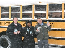 Gennessee Intermediate School District transportation employees distribute water and filters to Flint residents. Shown here from left to right are Chad Sexton, director of transportation services, Tonya Williams, dispatcher, and Michael Panek, transportation coordinator.