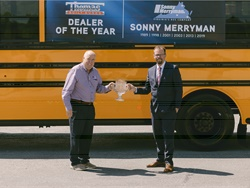 Floyd Merryman, president and CEO of Sonny Merryman (shown left), received the 2019 Dealer of the Year award from Caley Edgerly, president and CEO of Thomas Built Buses. Photo courtesy Thomas Built Buses