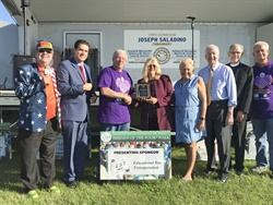 Joined by dignitaries and event organizers, Educational Bus Transportation Vice President of Operations Patti Royce-Moser (center), receives an award of appreciation from the Society of St. Vincent de Paul for Educational Bus Transportation's sponsorship of the recent Friends of the Poor Walk/Run.