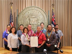 Hawaii Gov. David Ige (shown center right in red shirt), joined by staff members from school bus service providers Roberts Hawaii and TransPar, and officials from the Hawaii State Department of Education, recognized National School Bus Safety Week with a proclamation ceremony.