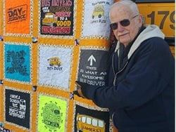 Larry Leverton has been a dedicated school bus driver for 60 years. He currently transports students for Lamers Bus Lines. He is shown here with a quilt created by his fellow bus drivers.