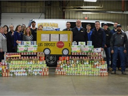 "Leonard Bus Sales' ""Giving Thanks and Giving Back"" includes a program that provides meals to children in need, a holiday canned food drive, and annual direct contributions to food banks. Shown here is the sales team with some of the food it donated to local food banks."