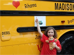 A student shows love for the bus during a Love the Bus event at Alabama dealership Transportation South.