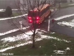 A Massachusetts school bus is shown on video sliding backward on an icy road and hitting a mailbox and a car. No one was hurt. Screen shot from video by Cheryl Katz via Boston 25 News