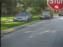 School bus video shows a motorist in Missouri veering around a stopped car and driving onto the lawn to pass a stopped school bus. Screenshot from bus video posted on Parkway School District's Facebook page.
