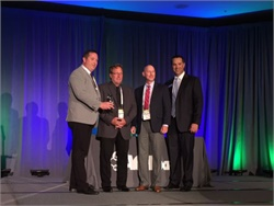 North Kansas City Schools' Dan Clemens (left), John Ray, and Lon Waterman accept the Transit and Mobility award from ACT Expo official Eric Neandross.