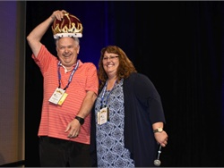 "Pam McDonald, president of CASTO, honored a male and female driver in the audience who have the longest school bus driving careers with crowns. Here, Donald Hain from San Marcos Unified School District takes his crown and accepts the title of ""king"" for the day."