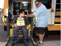 Former Newport-Mesa (Calif.) Unified School District bus driver Steve Black operates a wheelchair lift to help a student board the bus. (Black is now a dispatcher for the district.)