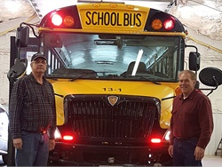 Red LEDs just above the bumper of a bus are framed by Ken Padget (left) and Dan Roberts of Davis County Community School District.