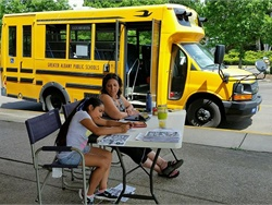 New bus riders and their families can take a spin on a Bend-La Pine Schools school bus. Shown here are a student and a driver trainer at an event held at another Oregon district that let students and parents see the school bus last summer.
