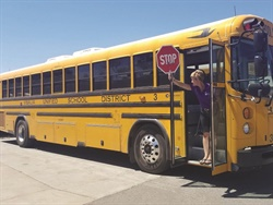 Sabine Konrad, a driver instructor for Visalia (Calif.) Unified School District, demonstrates how drivers should stick out the stop sign and check both directions for hazards before deboarding the bus. Photo courtesy Mary Ward