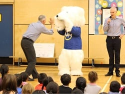 At the 2018 grant winner presentations, Buddy the Bear, United to End Bullying's mascot, gave a high-five to the principal of an elementary school in Surrey, British Columbia.