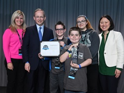 "Holly Grove Middle School students (shown center from left to right) Boston Harol, Evan Kruger, and Reanna Robertson received the top award for the Samsung ""Solve for Tomorrow"" contest after developing a flashing sign to improve school bus stop safety. They are shown here with Holly Grove Middle School teacher Debra Schelin (left), Dr. David Steel, Samsung's executive vice president and head of corporate affairs, and Ann Woo, Samsung's senior director of corporate citizenship."