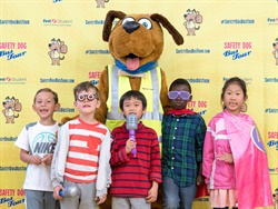 Students can pose with Safety Dog, First Student's mascot, during tour stops. Shown here are students posing with Safety Dog during the 2018 tour.