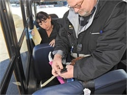 Greenville County (S.C.) Schools' Special Needs Physical Performance Test (SNPPT) for aides and drivers is composed of 11 standards. Shown here, Teena Mitchell (left), special-needs transportation coordinator for the district, tests a driver on SNPPT standard number 7, which is securing cam straps around a seat and securing a safety vest within three minutes.