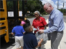 San Antonio ISD school bus driver Rosie Guadarrama and Nathan Graf, the district's director of transportation, pass out books to students as part of a program to promote summer reading.