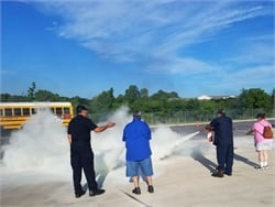 In a San Antonio ISD training event, school bus drivers and other employees rotated through 10 stations, one of which had live fires for fire extinguisher training.
