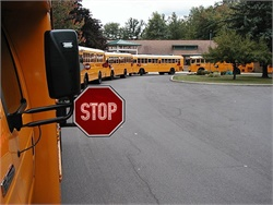 The New York Association for Pupil Transportation advises the public that state law requires all vehicles to come to a full stop when approaching a school bus that has its red lights flashing. Photo by Michael Dallessandro