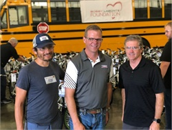 "Bobby Labonte (shown right, with ""Fast"" Freddie Rodriguez and Caley Edgerly, center) visits Thomas Built Buses for Bike Build Day, where bicycles were assembled and later donated to local High Point, North Carolina, nonprofits."