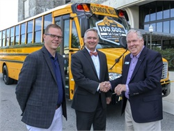 Caley Edgerly (left) of Thomas Built Buses and Floyd Merryman (right) of the Sonny Merryman dealership present the 100,000th Saf-T-Liner C2 school bus to Mark Miear of Montgomery County (Va.) Public Schools.