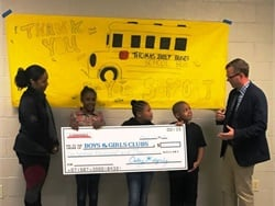 Caley Edgerly, the president and CEO of Thomas Built Buses (right), presents a pledge for $100,000 to the Boys & Girls Clubs of Greater High Point.